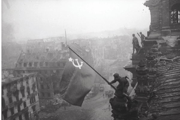 Red army soldiers raising the soviet flag over the Reichstag in Berlin.