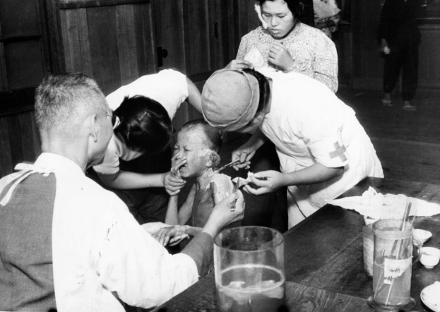 An atomic bomb survivor cries as he receives a treatment at temporary hospital set at Shin Kozen Elementary School in August 1945