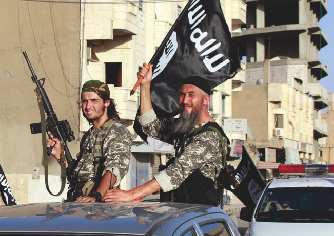 """01 Jul 2014, Ar Raqqah, Syria --- Militant Islamist fighters wave flags as they take part in a military parade along the streets of Syria's northern Raqqa province June 30, 2014. The fighters held the parade to celebrate their declaration of an Islamic """"caliphate"""" after the group captured territory in neighbouring Iraq, a monitoring service said. The Islamic State, an al Qaeda offshoot previously known as Islamic State in Iraq and the Levant (ISIL), posted pictures online on Sunday of people waving black flags from cars and holding guns in the air, the SITE monitoring service said. Picture taken June 30, 2014. REUTERS/Stringer (SYRIA - Tags: POLITICS CIVIL UNREST CONFLICT) --- Image by © STRINGER/Reuters/Corbis"""