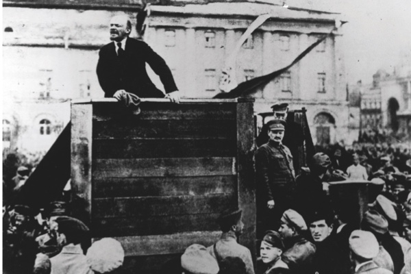 Russian revolutionary leader Vladimir Lenin (1870 - 1924) speaks to a crowd; fellow revolutionary Leon Trotsky (1879 - 1940) can be seen standing beside the platform on the right looking out over the crowd, Sverdlov Square, Moscow, May 5, 1920.  (Photo by Time Life Pictures/Mansell/Time Life Pictures/Getty Images)