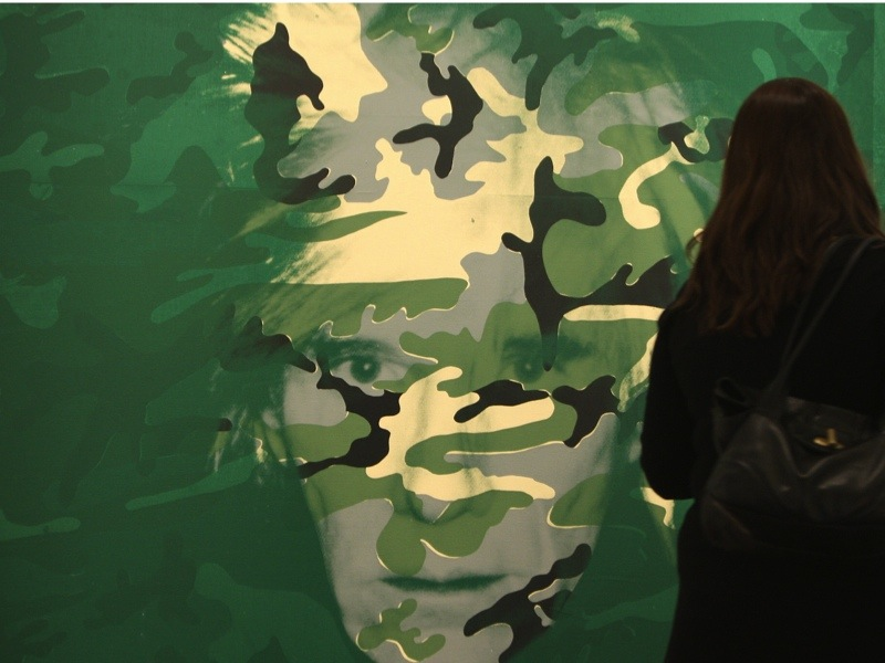 """A woman walks past the painting """"Sef Portrait (Green Camouflage)"""" by US artist Andy Warhol during a preview of Sotheby's fall sales of contemporary art in New York, 02 November 2007.  The painting, from his last series of self-portraits, has an estimated bid of nine to 12 million USD. Sotheby's fall sales will offer to bidders 37 lots of contemporary art, in New York on 14 November 2007. AFP PHOTO/Emmanuel DUNAND (Photo credit should read EMMANUEL DUNAND/AFP/Getty Images)"""