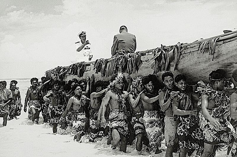 Prince Philip being brought ashore the island of Vaitupu in a large canoe by a group of people.