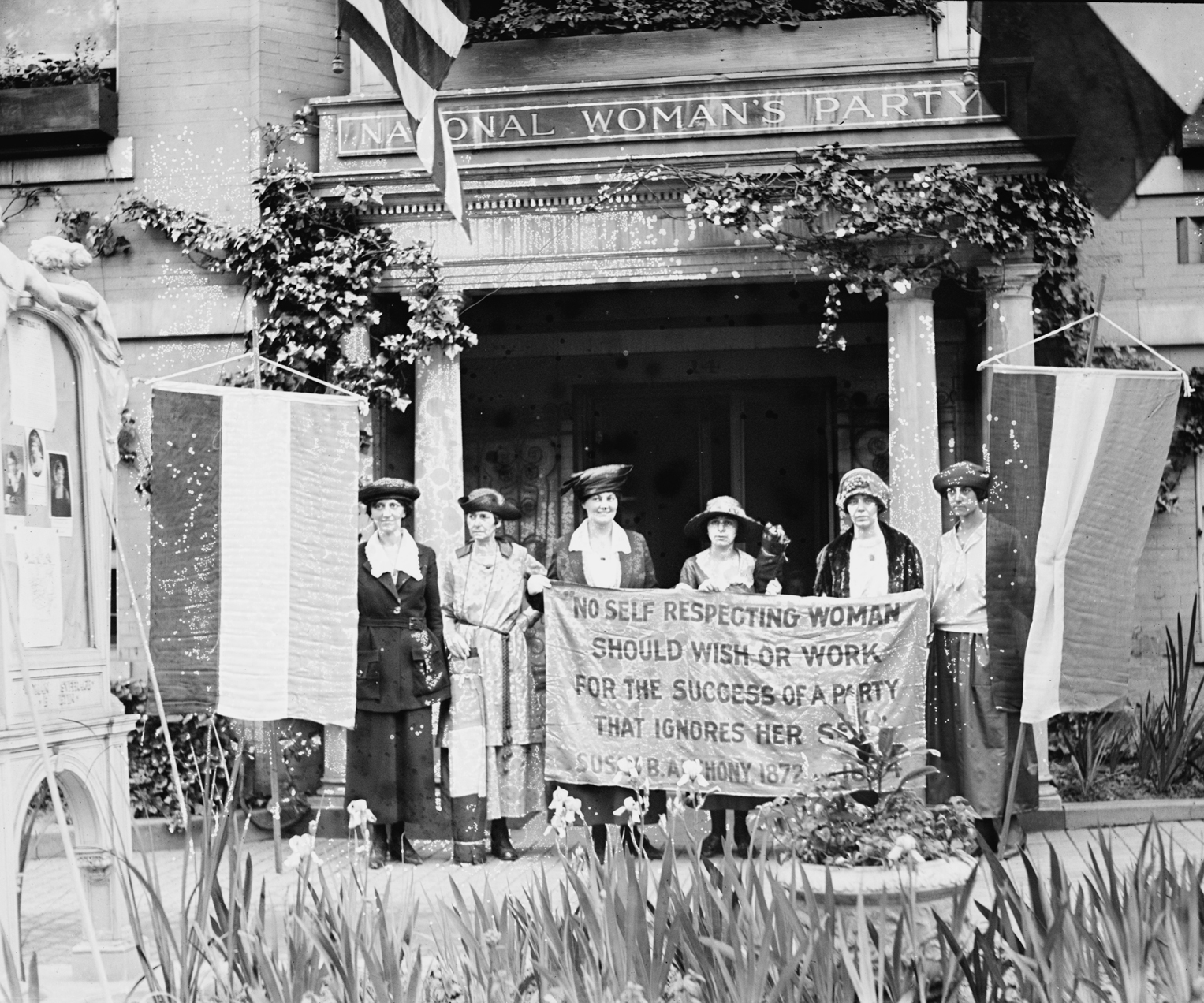 UNITED STATES - CIRCA 1900:  Suffragettes hold up banner in front of a building that has an architrave sign of the National Woman's Party; They claim to be ignored by the organization and hold up a protesting banner.  (Photo by Buyenlarge/Getty Images)