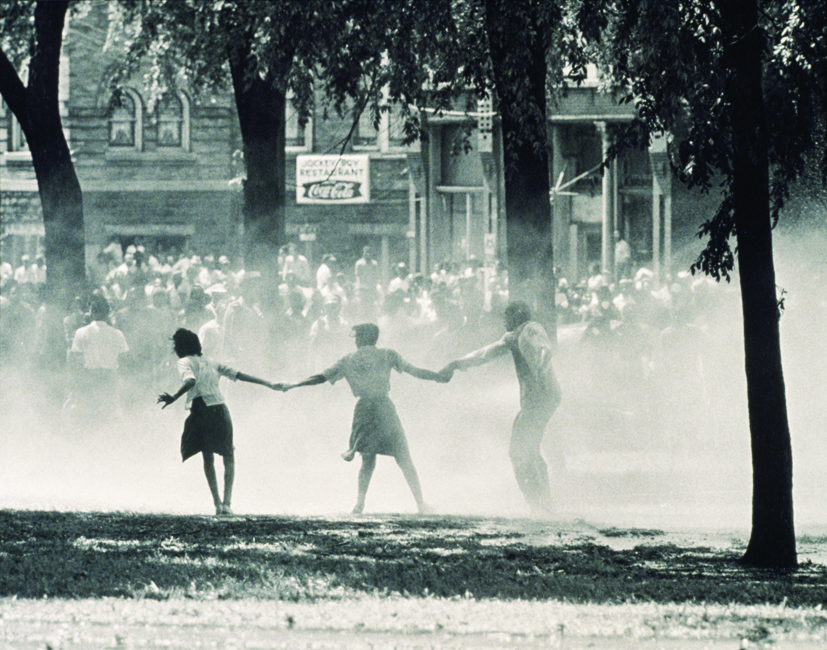 04 May 1963, Birmingham, Alabama, USA --- An African American man and two African American women hold hands and try to brace themselves against the harsh spray of a fire hose during an anti-segregation protest in Birmingham, Alabama, May 4, 1963. Against the 3,000 protesters, police released dogs, attacked with electric cattle prods and used water sprayed with the strength to rip bark off of trees. These images were televised cross the nation. --- Image by © Bettmann/CORBIS