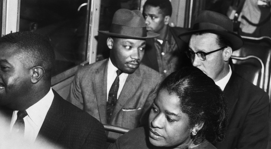 21 Dec 1956, Montgomery, Alabama, USA --- Dr. Martin Luther King, Jr. (center) rides the Montgomery bus with Rev. Glenn Smiley (right) of Texas. In 1955, black activists formed the Montgomery Improvement Association to boycott the segregated transit system and chose Dr. King as their leader. A year later, the African Americans of Montgomery, Alabama, achieved their goal of desegregation of the city's buses. --- Image by © Bettmann/CORBIS