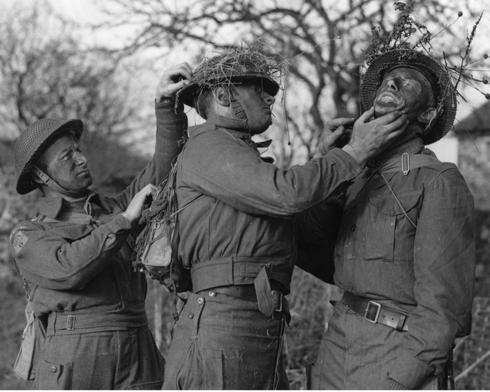 January 1942:  Home Guards smear on green paint and attach camouflage to each other during a camouflage training course at Fieldcraft School in South-Eastern Command.  (Photo by Harry Todd/Fox Photos/Getty Images)