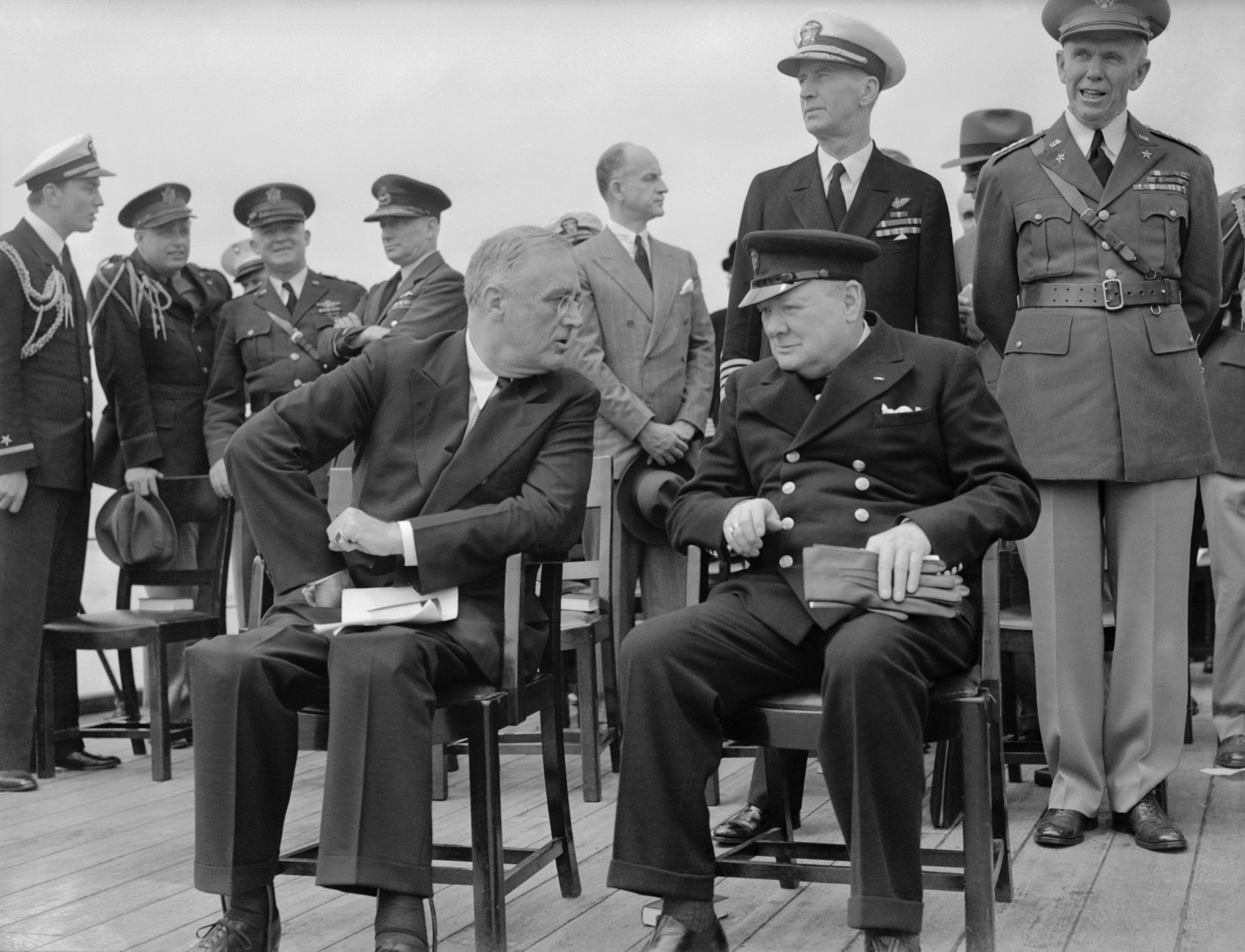 Atlantic Conference Between Prime Minister Winston Churchill And President Franklin D Roosevelt 10 August 1941, The President of the United States, Franklin D Roosevelt, and the Prime Minister of the United Kingdom, Winston Churchill are seated on the Quarterdeck of HMS PRINCE OF WALES. They are chatting following a Sunday service, during the Atlantic Conference, 10 August 1941. Immediately behind them are Admiral E J King, USN and General Marshall, US Army. The President's sons, Ensign Franklin Roosevelt Jr USNR and Captain Elliot Roosevelt USAAF, along with General Arnold, USAAF, Air Chief Marshal Sir Wilfred Freeman RAF are conversing to the left of the image, 10 August 1941. (Photo by Lt. L C Priest/ IWM via Getty Images)