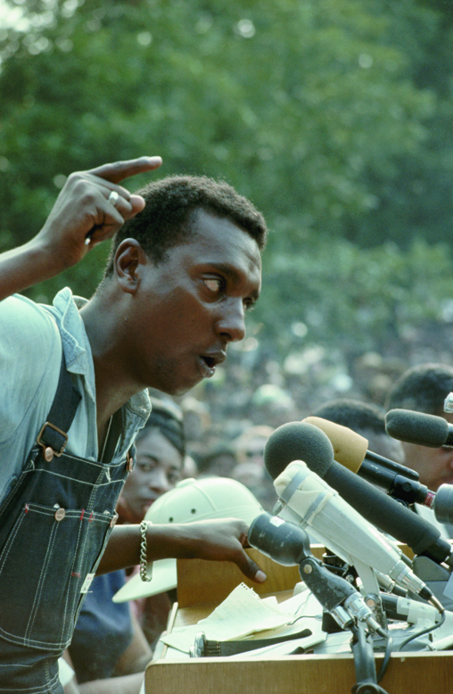 """June 1966, Jackson, Mississippi, USA --- SNCC leader Stokely Carmichael speaks to the crowd during the final rally of the March Against Fear at the Mississippi State Capitol. During the speech Carmichael introduced the slogan """"Black Power!"""" to a wider audience, exposing the rift between him and Martin Luther King Jr. --- Image by © Flip Schulke/CORBIS"""
