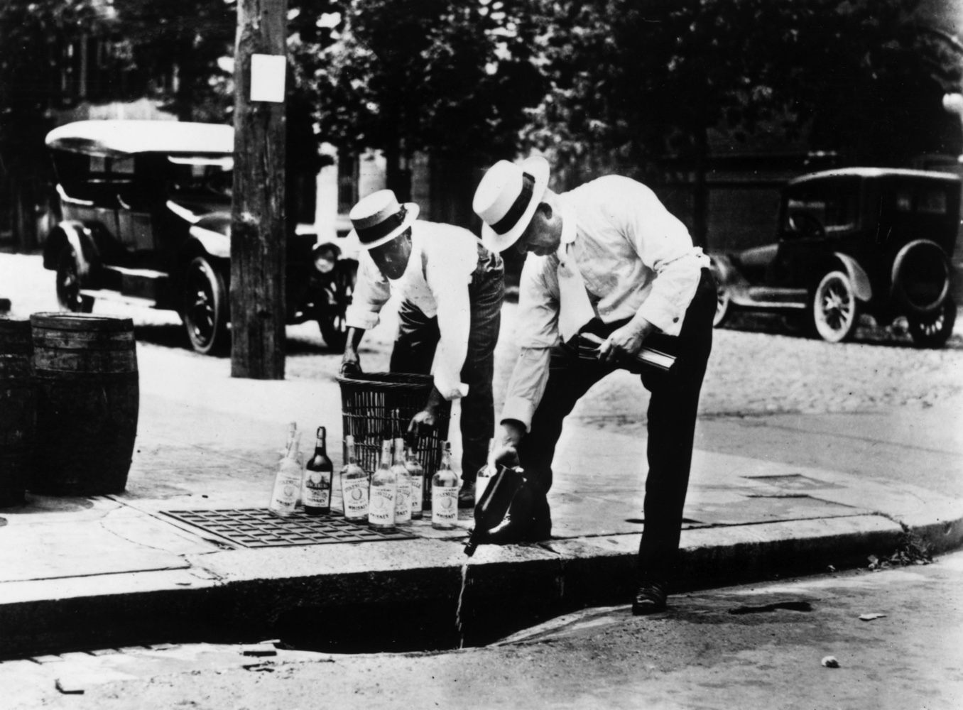 Two men pour alcohol down a drain during prohibition in the United States, c1920.