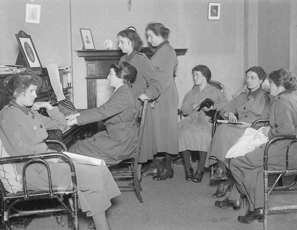 Members of the WAAC pictured in January 1918, singing around a piano during their leisure time. (Photo by Topical Press Agency/Getty Images)