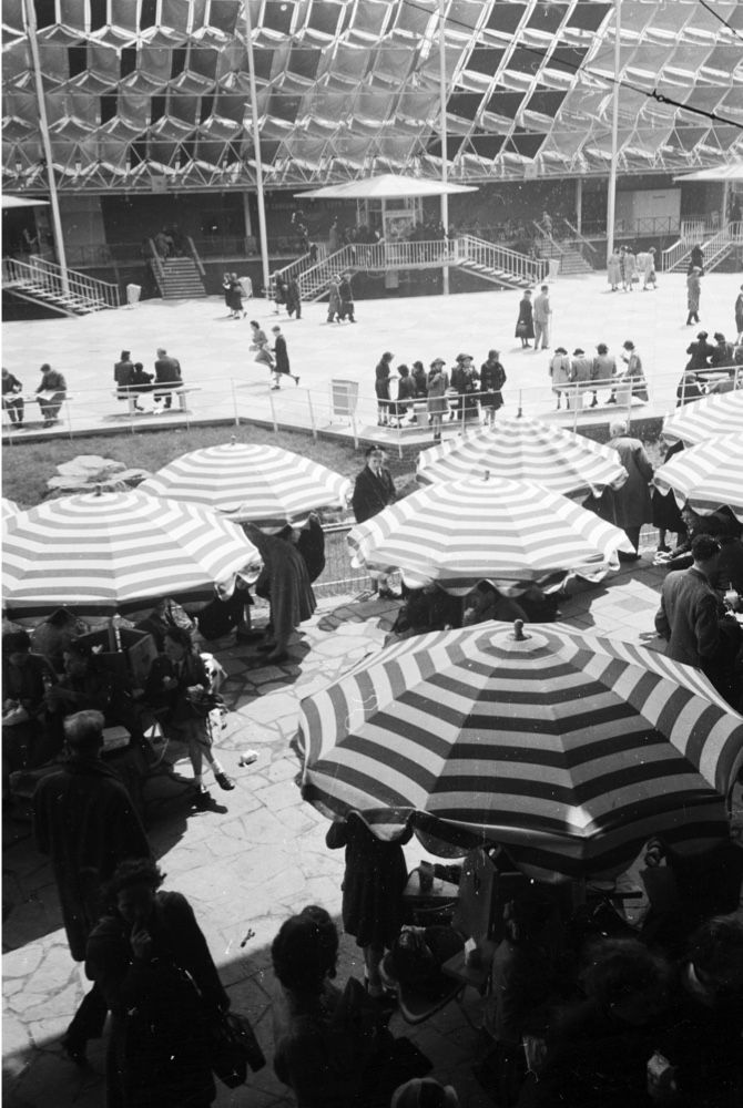 Visitors to the 1952 Festival of Britain sit beneath colourful, striped umbrellas. (Ernst Haas/Getty Images)