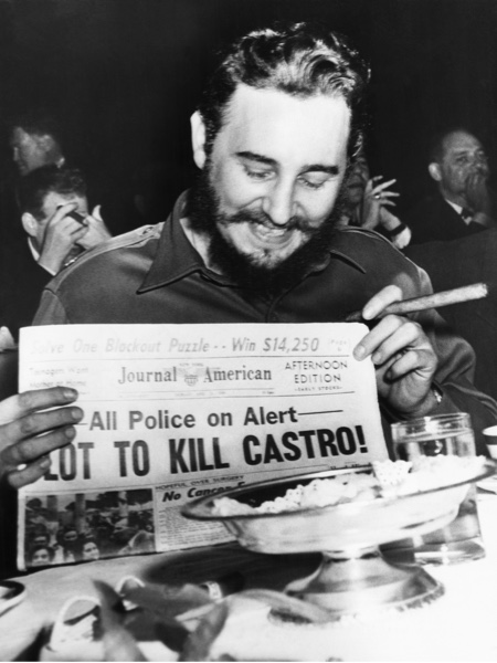 Fidel Castro holds up a newspaper headlining the discovery of a plot to kill him