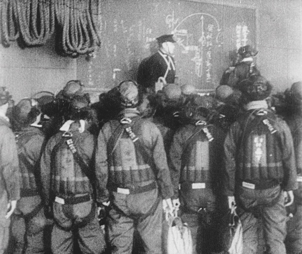 (Original Caption) Aboard a Japanese aircraft carrier, a naval officer gives a group of bomber pilots last minute instructions before they took off to blast American installations at Pearl Harbor on December 7, 1941. This picture, taken from a Japanese newsreel obtained by the War Department and released by the OWI, is part of a documentary film issued by the Japs giving their version of the start of the war.
