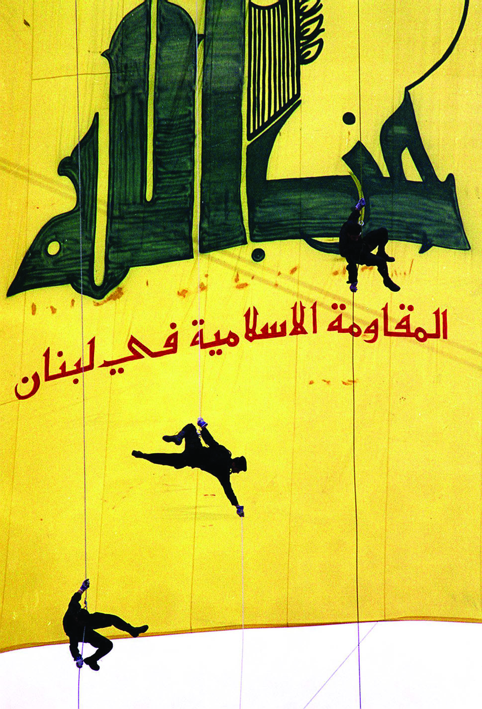 "BEIRUT, LEBANON - JANUARY 15: Black-clad Hezbollah militants descend in front of a giant banner reading ""Hezbollah, the Islamic Resistance in Lebanon,"" 15 January in a southern suburb of Beirut to mark ""International Qods (Jerusalem) Day,"" which was first established by Iran after the 1979 Islamic Revolution to show solidarity with the Palestinians against Israel. The Iranian-backed Hezbollah movement spearheads the armed struggle to oust Israeli occupation forces from southern Lebanon. (Photo credit should read HAYTHAM MUSAWI/AFP/Getty Images)"