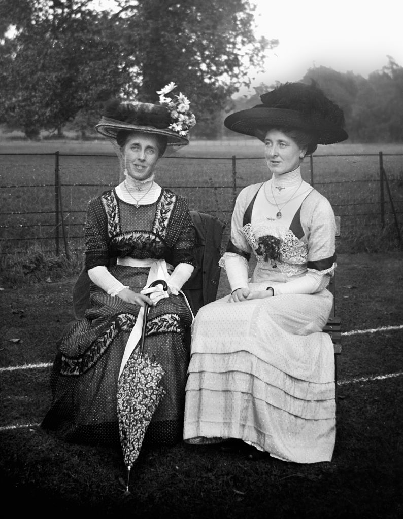 Two Victorian women sit on a park bench in England, ca. 1900 (Photo by Kirn Vintage Stock/Corbis via Getty Images)