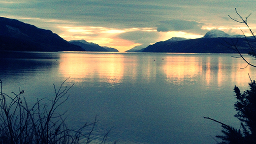 Idyllic Shot Of Loch Ness By Mountain Range Against Sunset Sky