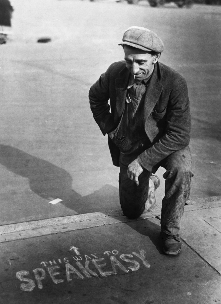 A potential customer examines an advertisement for an illegal drinking den or speakeasy during US prohibition in the 1920s.