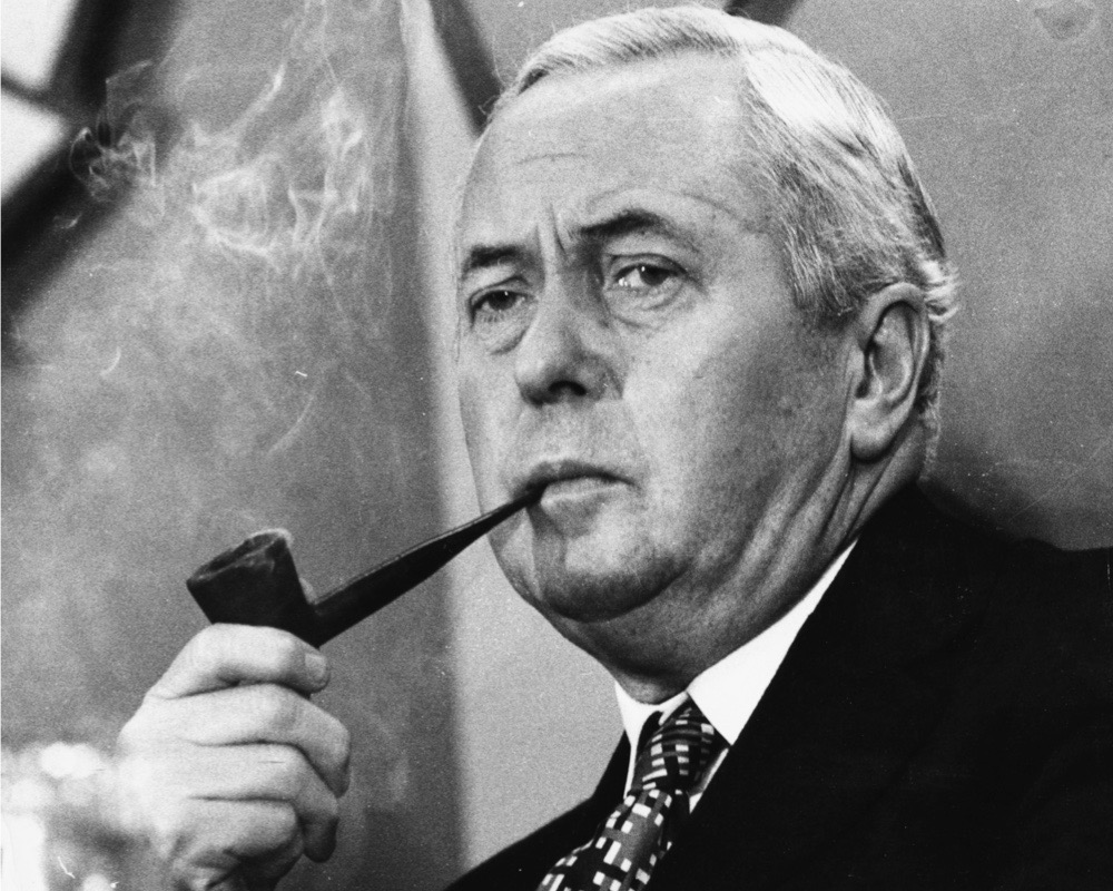 British Prime Minister Harold Wilson smoking his pipe, as he listens to journalists questions at the Labour Party election conference, Smith Square, London, October 4th 1974. (Photo by Monti Spry/Central Press/Getty Images)