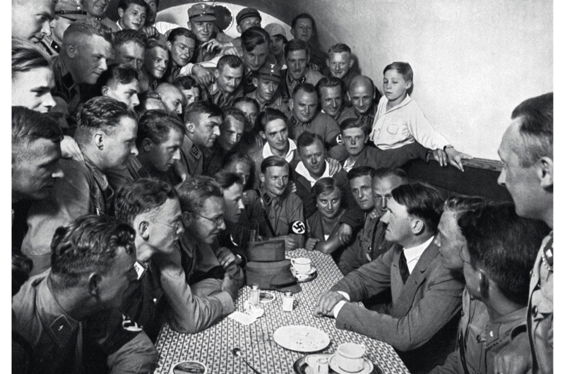 Nazi leader Adolf Hitler sits at a table facing a group of young uniformed National Socialists crowded into a small room in the 'Braune Haus' or Brown House, Munich, Germany, c1935. (Photo by Heinrich Hoffmann/Hulton Archive/Getty Images)