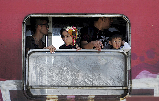 Migrants look out a window as they stand on board a train to Serbia at a transit camp in Gevgelija, Macedonia, after entering the country by crossing the border with Greece, September 15, 2015. Two decades of frontier-free travel across Europe unraveled on Monday as countries re-established border controls in the face of an unprecedented influx of migrants, which broke the record for the most arrivals by land in a single day. Germany's surprise decision to restore border controls on Sunday had a swift domino effect, prompting neighbors to impose checks at their own frontiers as thousands of refugees pressed north and west across the continent while Hungary sealed the main informal border crossing point into the European Union. REUTERS/Ognen Teofilovski - RTS1613