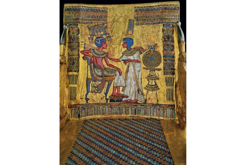 The king is seen sitting casually on an armless chair, while the queen anoints him with perfumed oil. On her head is a 'Nubian' wig, a short hairstyle that became popular with women during the Amarna Period.