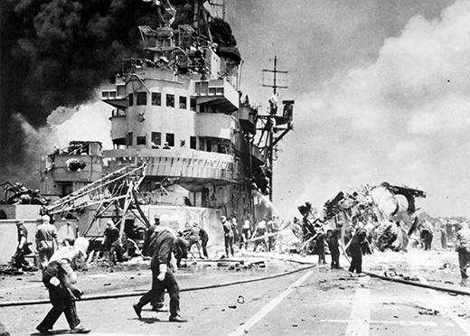WORLD WAR II: KAMIKAZE. Firefighting crews aboard a British Pacific Fleet aircraft carrier hit by a Japanese kamikaze attack off the coast of Okinawa, 22 June 1945.