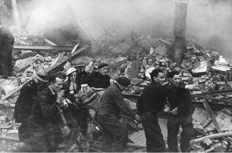 Blitz in London -- a casualty who has just been rescued from the rubble is carried on a stretcher to an ambulance.   (3 of 3)      Date: 1940s