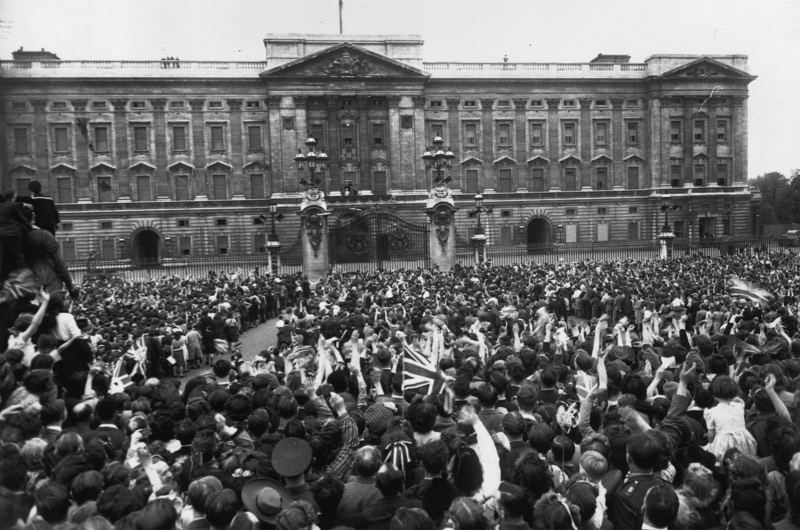 8th May 1945:  VE day, held to commemorate the official end of Britain's involvement in World War II, is celebrated by a crowd outside the gates of Buckingham Palace. The King and Queen, with Princess Elizabeth and Princess Margaret appear on the palace balcony to greet the crowd.  (Photo by Harry Todd/Fox Photos/Getty Images)