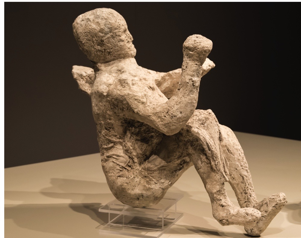 TORONTO, ONTARIO, CANADA - 2015/08/21: Plaster cast body of a person killed by the eruption of Mount Vesuvius at Pompeii in 79 A.D on display at the Royal Ontario Museum. The person is in a sitting posture. The city of Pompeii was an ancient Roman town in Italy which was mostly destroyed and buried under ash and pumice in the eruption of Mount Vesuvius in 79 AD. (Photo by Roberto Machado Noa/LightRocket via Getty Images)