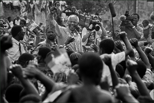 South Africa.  Natal. Lamontville.  Mandela surrounded by supporters and newsmen gives a clenched fist salute at an ANC rally.  1994