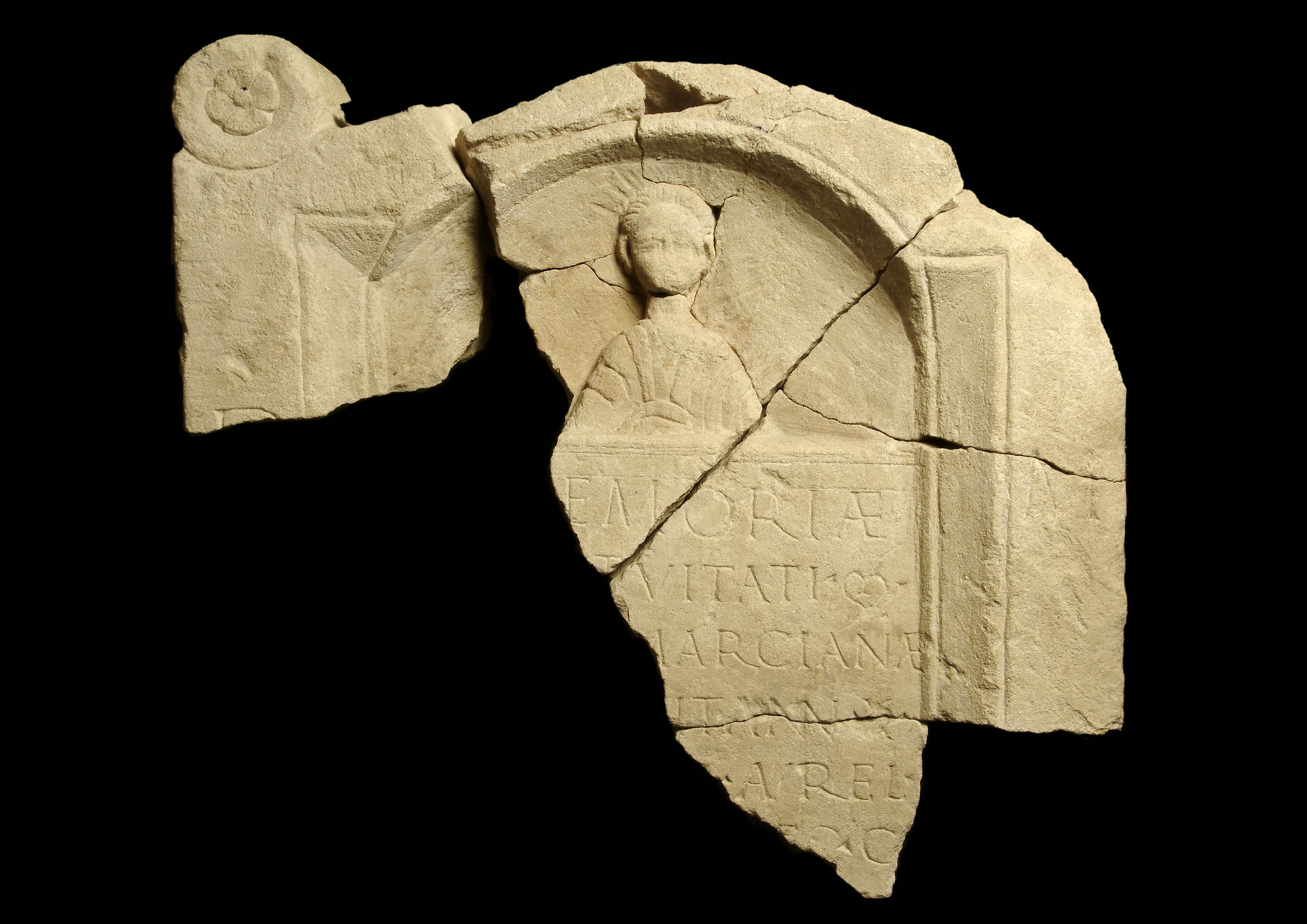 A tombstone of a 10-year-old girl, Marciana. It was found during excavations of the city wall in 1979, which revealed that the wall was partly composed of reused monumental masonry including fragments of tombstones. The tombstone has an inscription beneath Marciana's bust and a D M on the border of the stone. (© Museum of London)