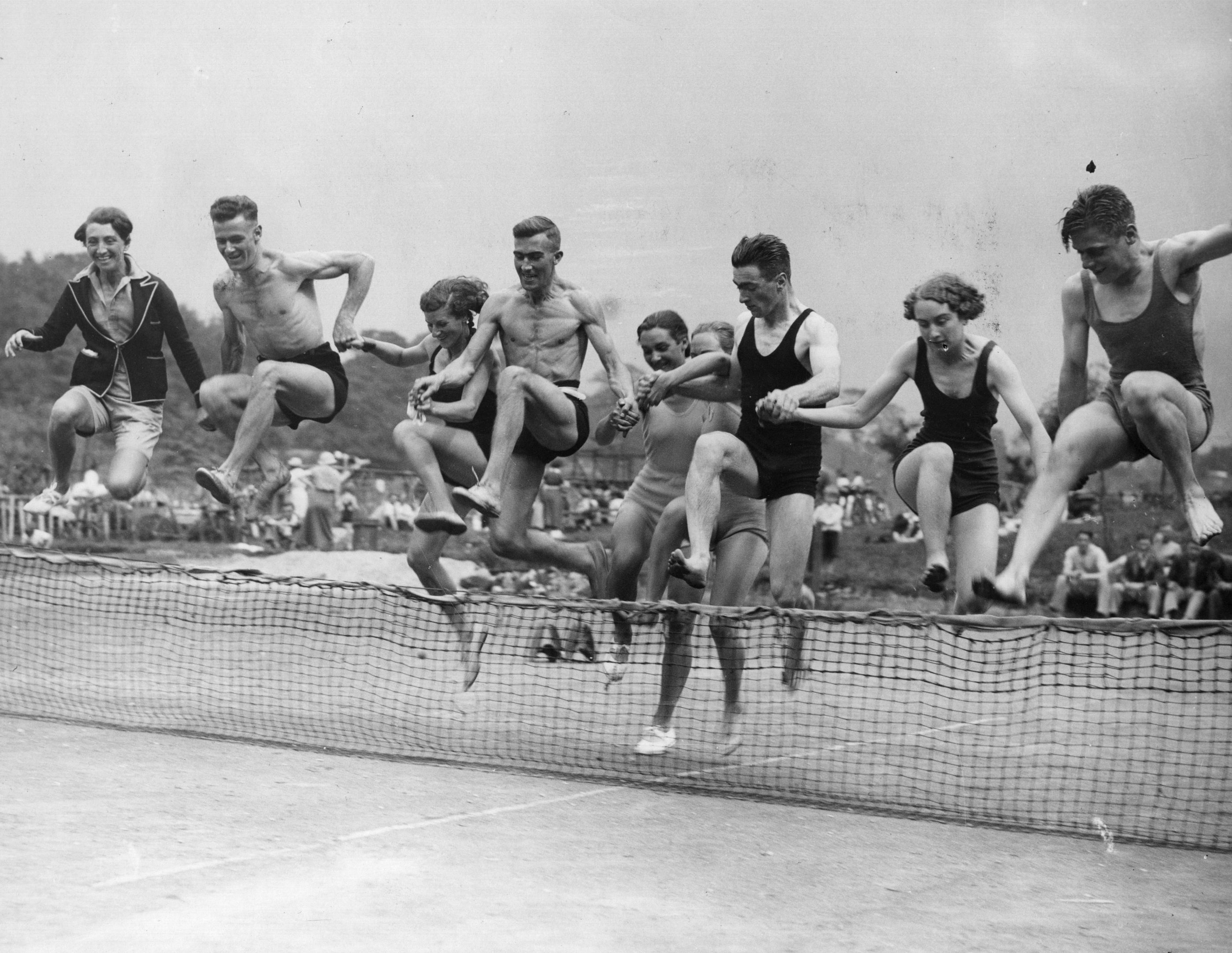 Sunbathers enjoy some fun and games at a tennis court near a lido at Castle Mill, Cheshire, August 1936