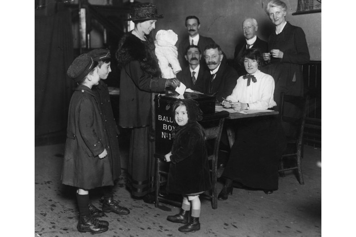 """A woman casts her vote, accompanied by her children, in December 1918. Women weren't as """"timid and uncertain at the polling stations as had generally been anticipated"""", reported 'The Times'. (Photo by Topical Press Agency/Getty Images)"""