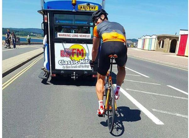 A man cycling behind a tram