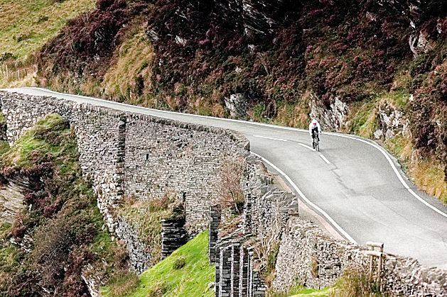Cyclist riding fast on road in Bala North Wales