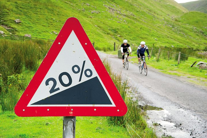 Cyclists ride past a 20% gradient sign on a cycling route in the Scottish Borders