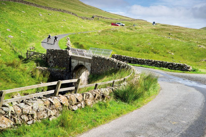 Two cyclists descend a hill towards a stone bridge in the Scottish Borders