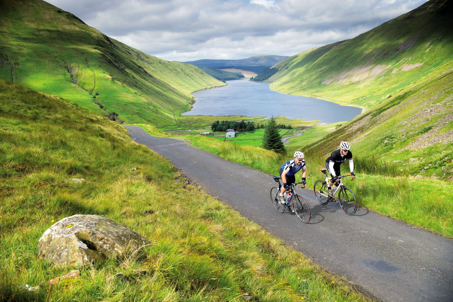 Two cyclists climbing in the Scottish Borders with a loch in background
