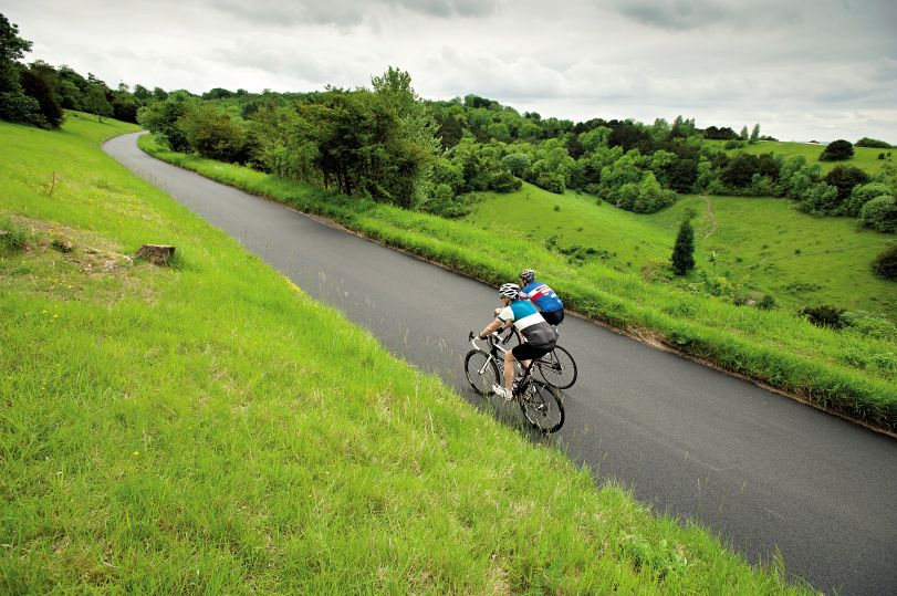 Two cyclist ride up the iconic Box Hill climb near Dorking in Surrey