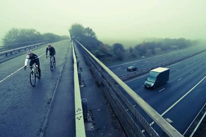 Two cyclists cross the M4 motorway on a bridge
