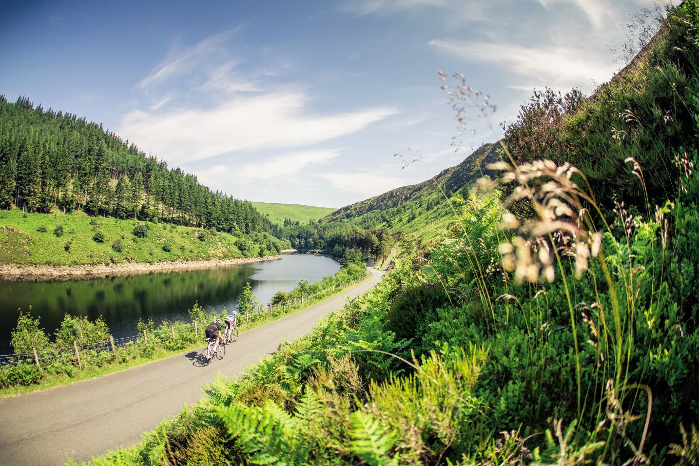 Two cyclists ride past a reservoir in the Elan Valley, Wales