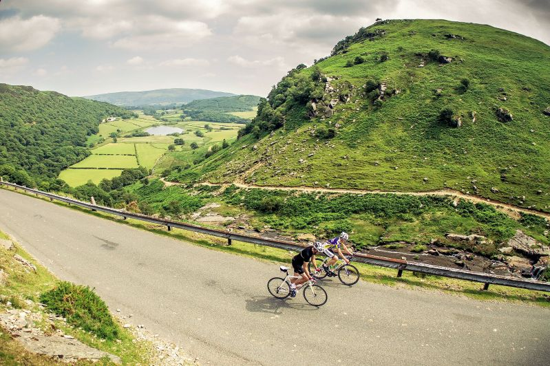 Two cyclists on a road climb in the Elan Valley near Rhayader, Wales