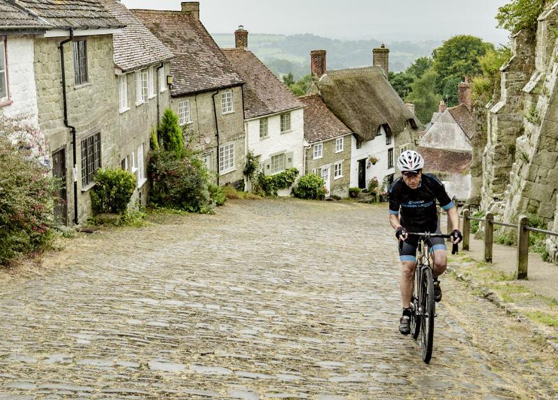 Cyclist climbs Gold Hill, Shaftesbury, Dorset on Kinesis bike