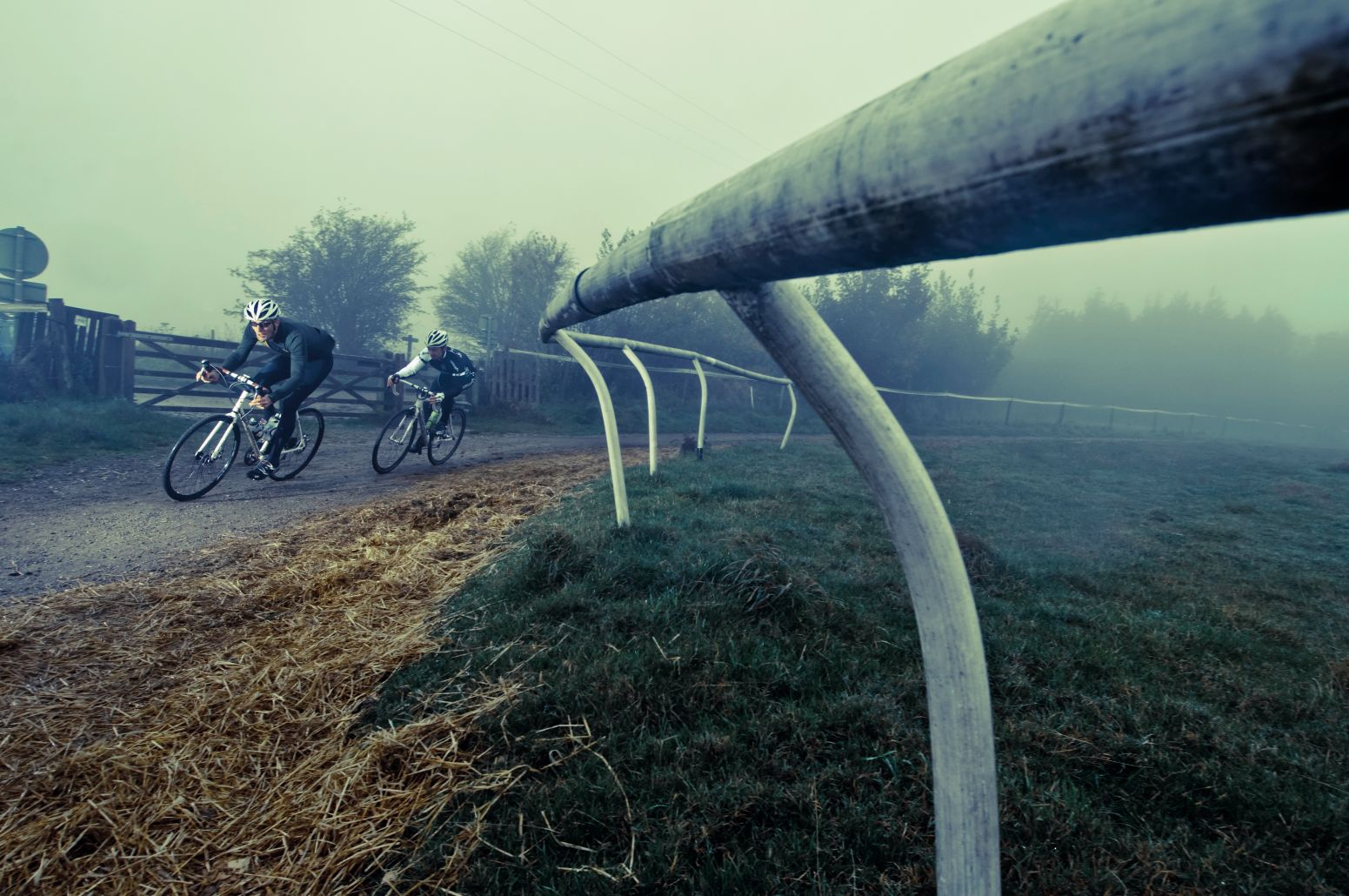Two cyclists riding fast on a racecourse