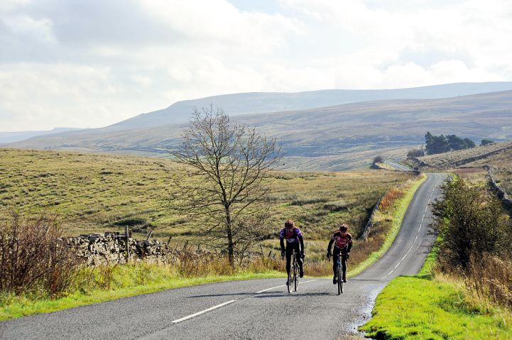 Two cyclists riding on an empty, straight road in the Yorkshire Dales