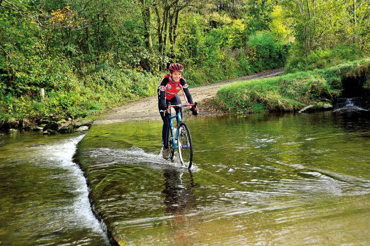 A cyclist rides through a ford in the North of England