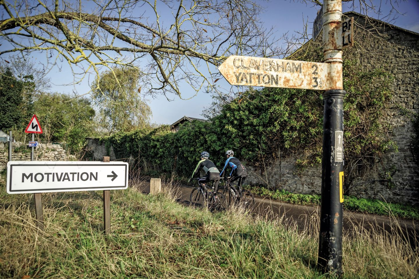 Two cyclists ride past direction signs in Somerset