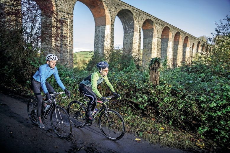 Two cyclists ride past Pensford Viaduct near Bristol