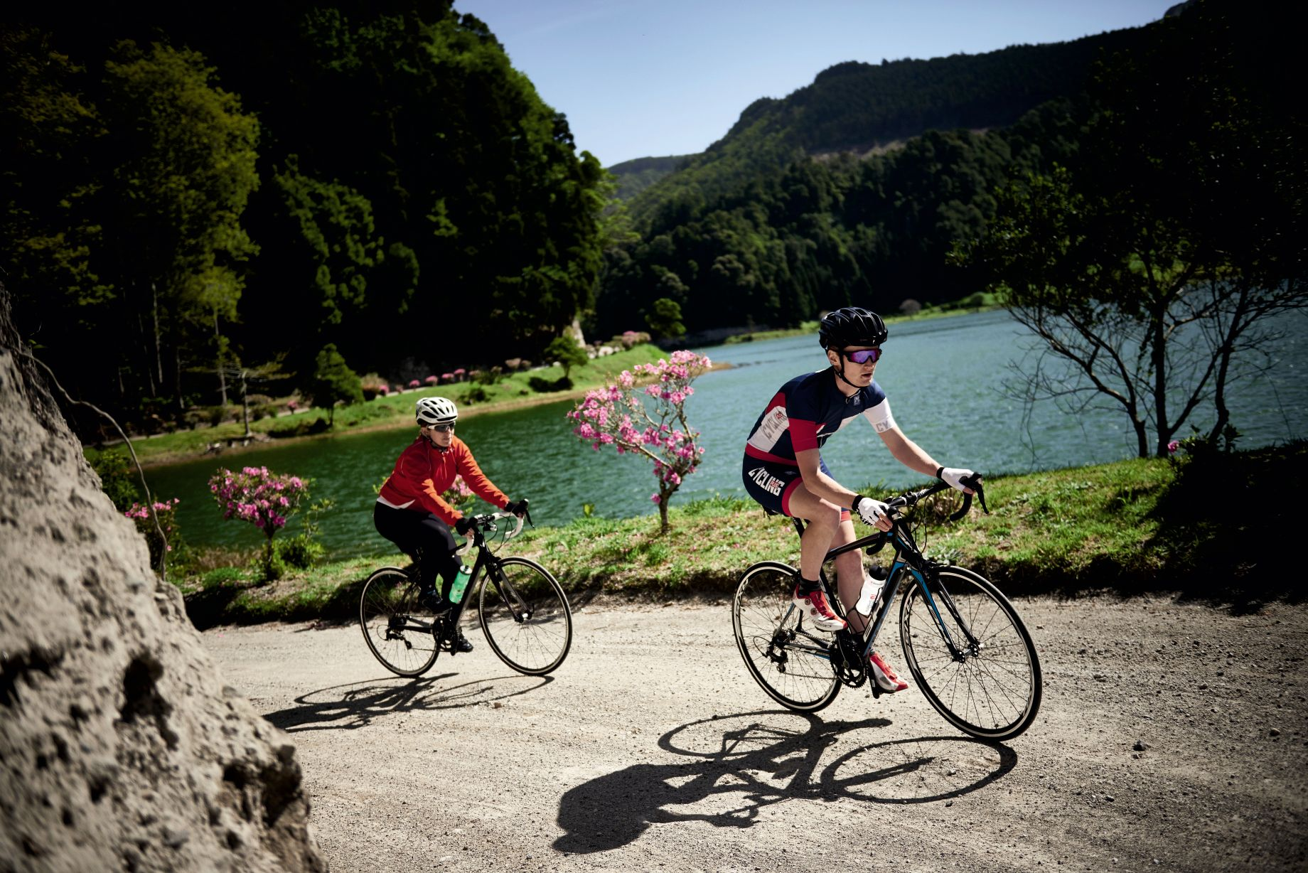 Two cyclists riding in the Azores with a lakeland background