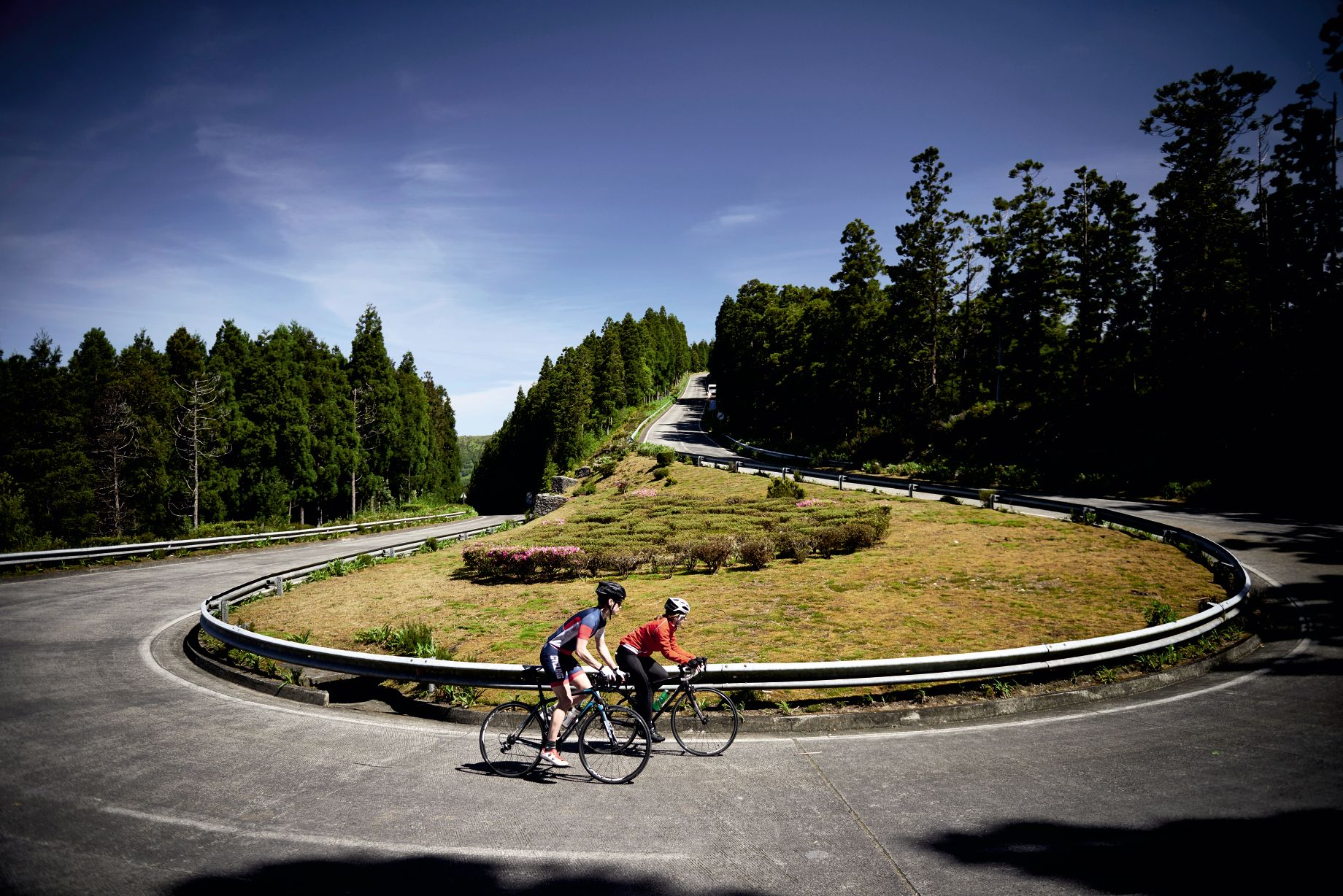 Two cyclists climbing a hill in the Azores. Hairpin bend